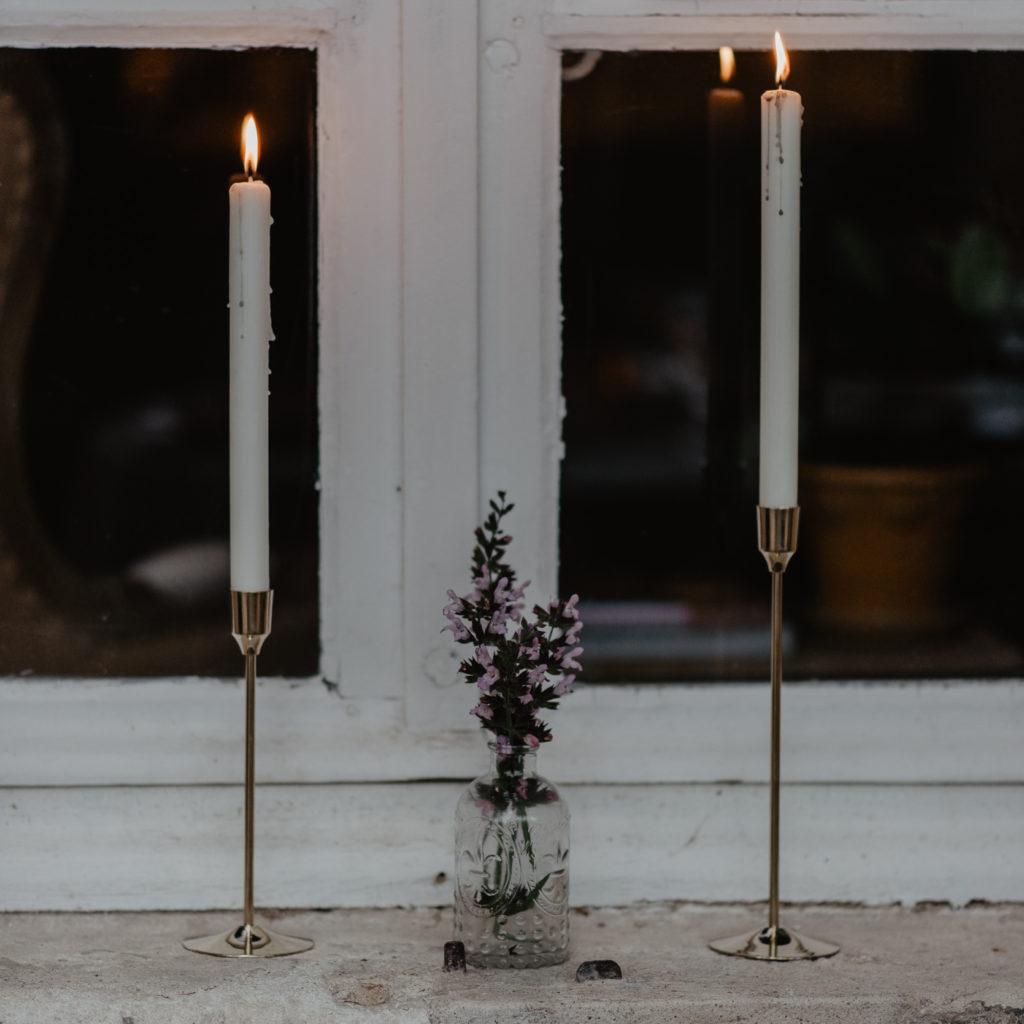 Twee kaarsen met in het midden een paarse bloem