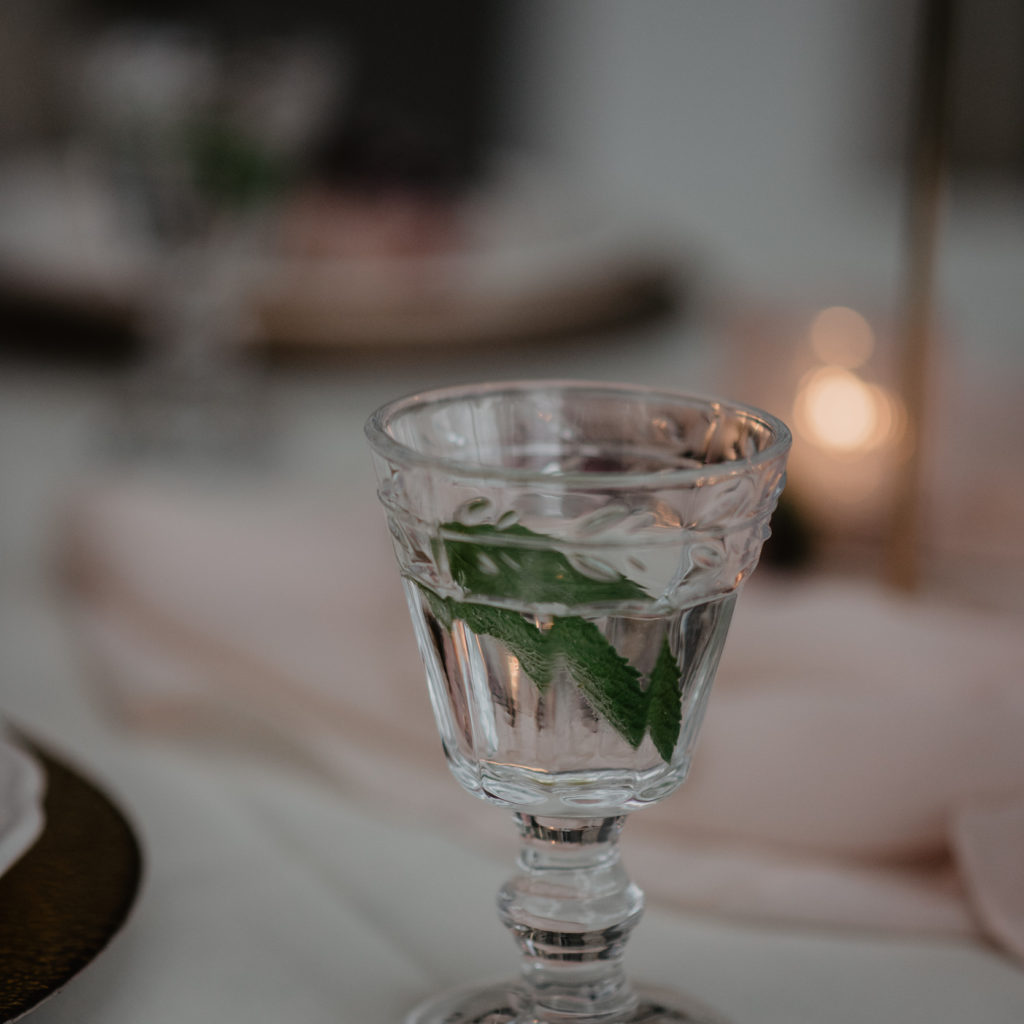 Drankje in vintage glas op tafel met roze tinten