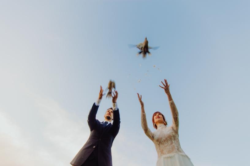 bruidspaar die duiven loslaten