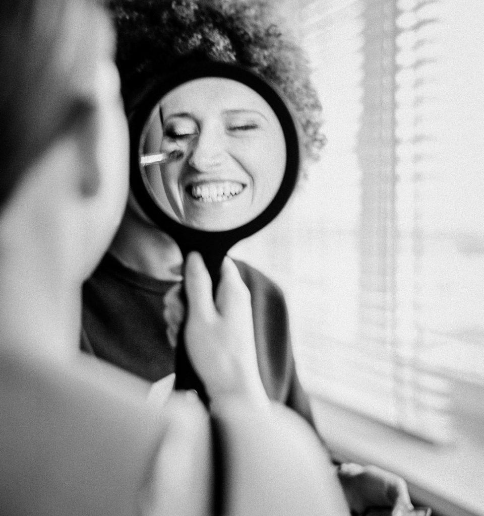 reflectie van bruid die opgemaakt wordt in spiegel