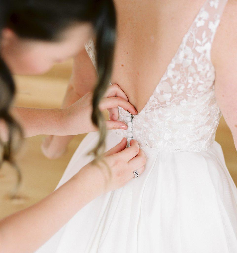 rug van bruid terwijl haar trouwkleed vastgemaakt wordt