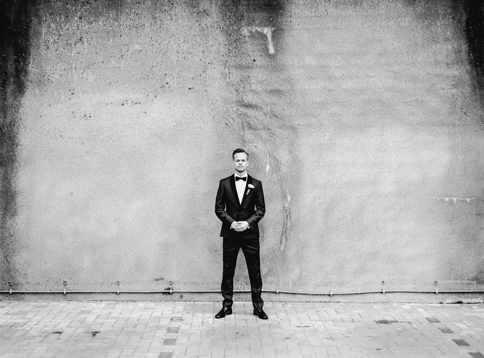 zwart-wit foto van bruidegom voor muur