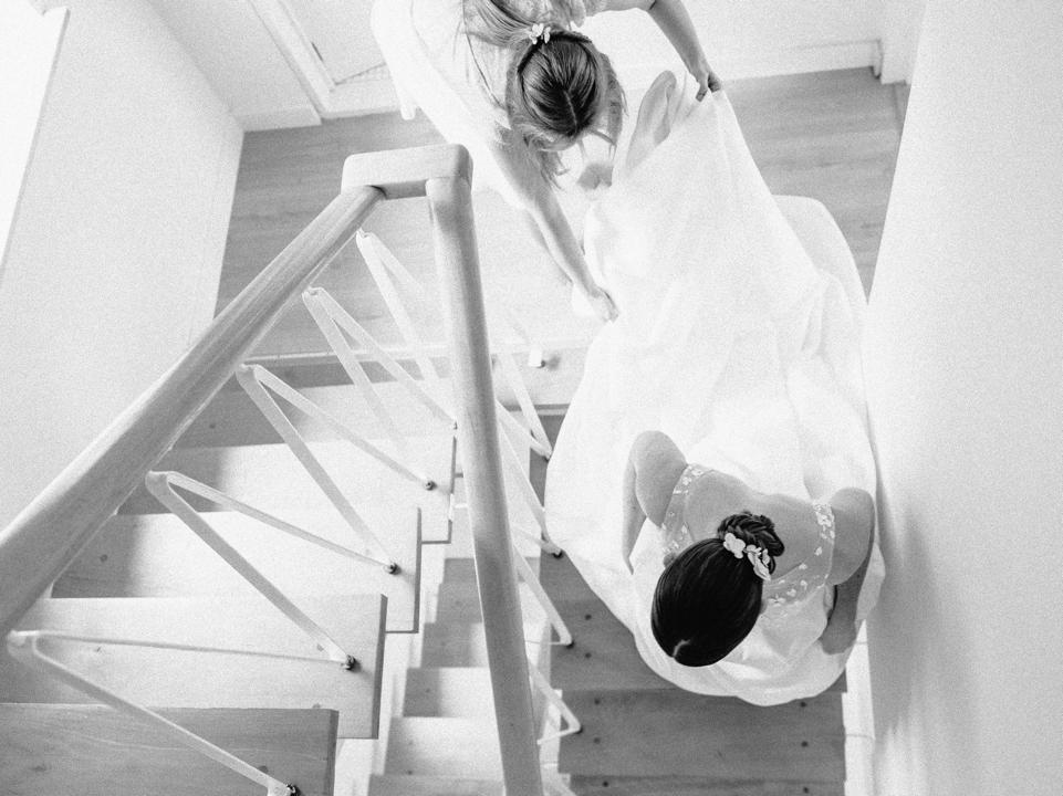 zwart-wit foto van bruid die de trap afwandelt