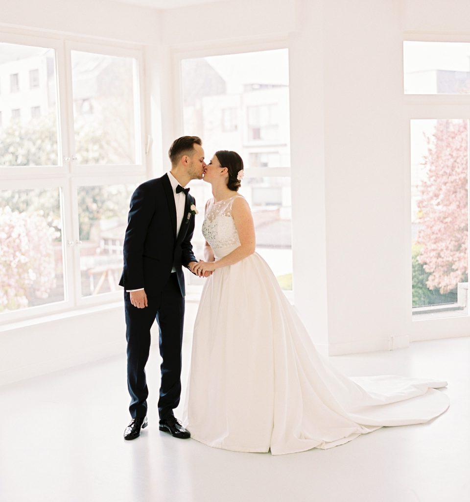 trouwfoto van kussend koppel in wit interieur