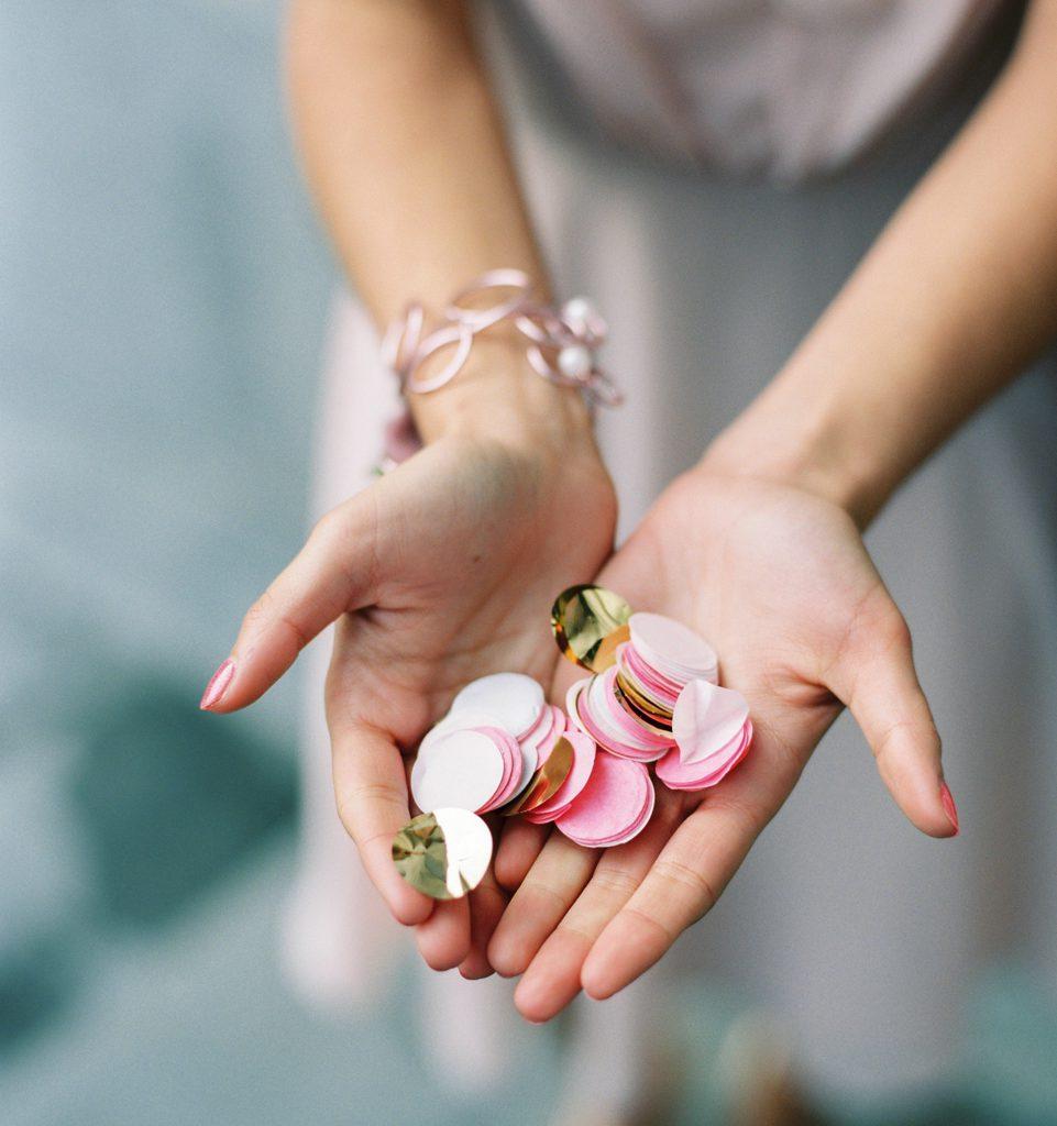 handen waarin roze, witte en gouden bolletjes confetti liggen voor trouw