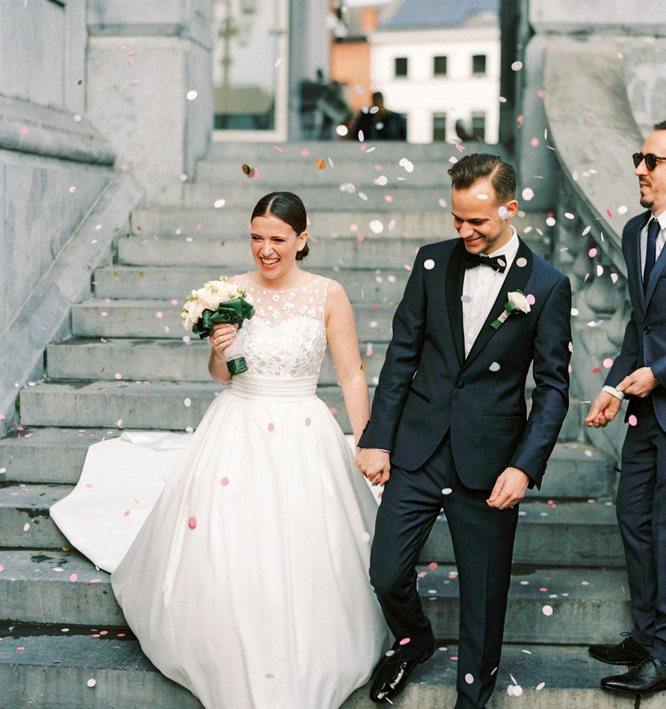 bruid en bruidegom die trap afwandelen met confetti die wordt gegooid