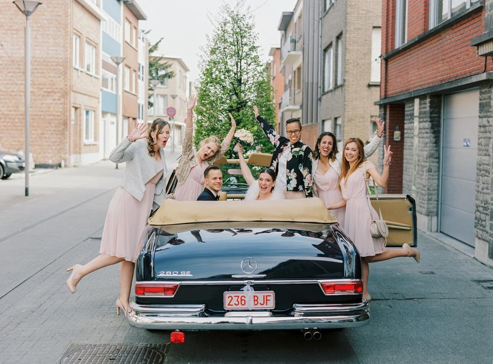 Bruid en bruidegom met bruidsmeisjes in wagen
