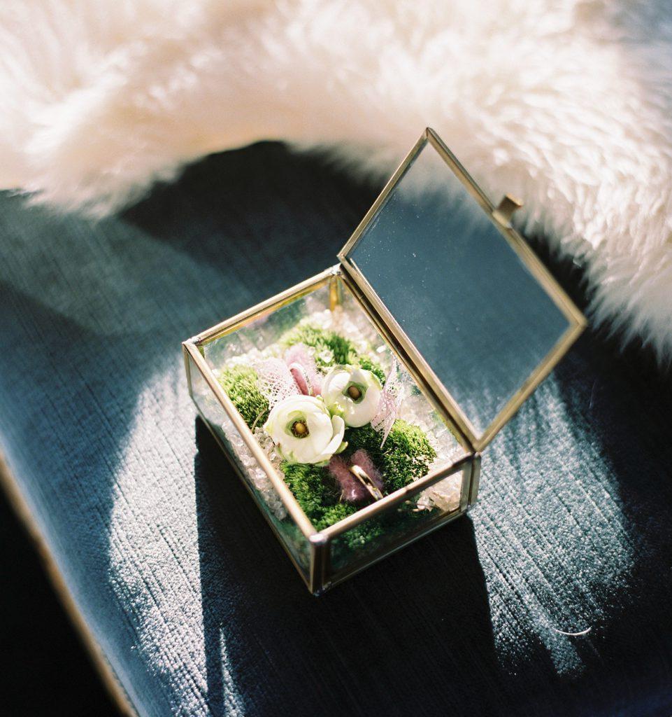 glazen doosje gevuld met mos en bloemen en trouwringen