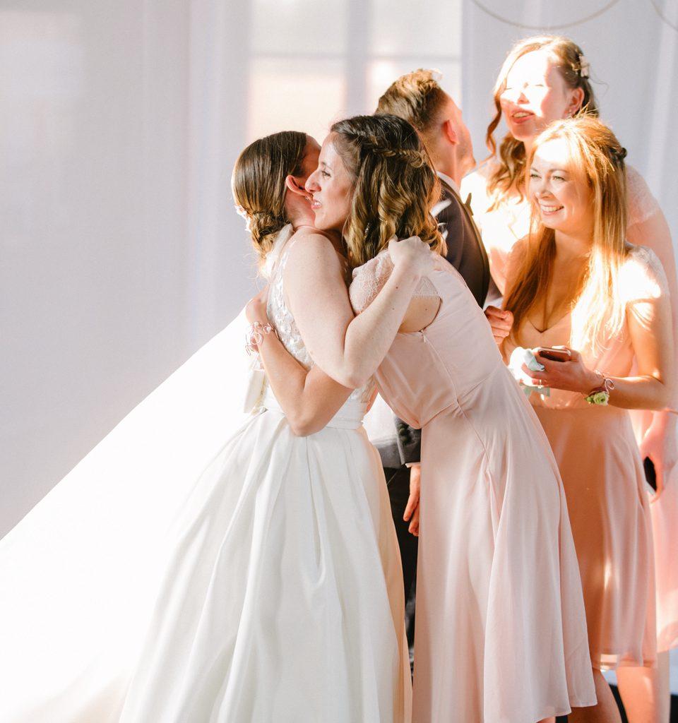 bruid wordt geknuffeld door bruidsmeisje