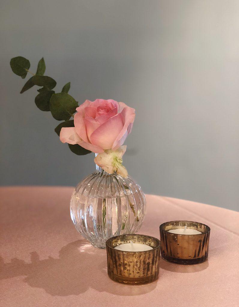 klein glazen vaasje met roze roos en twee theelichtjes ervoor