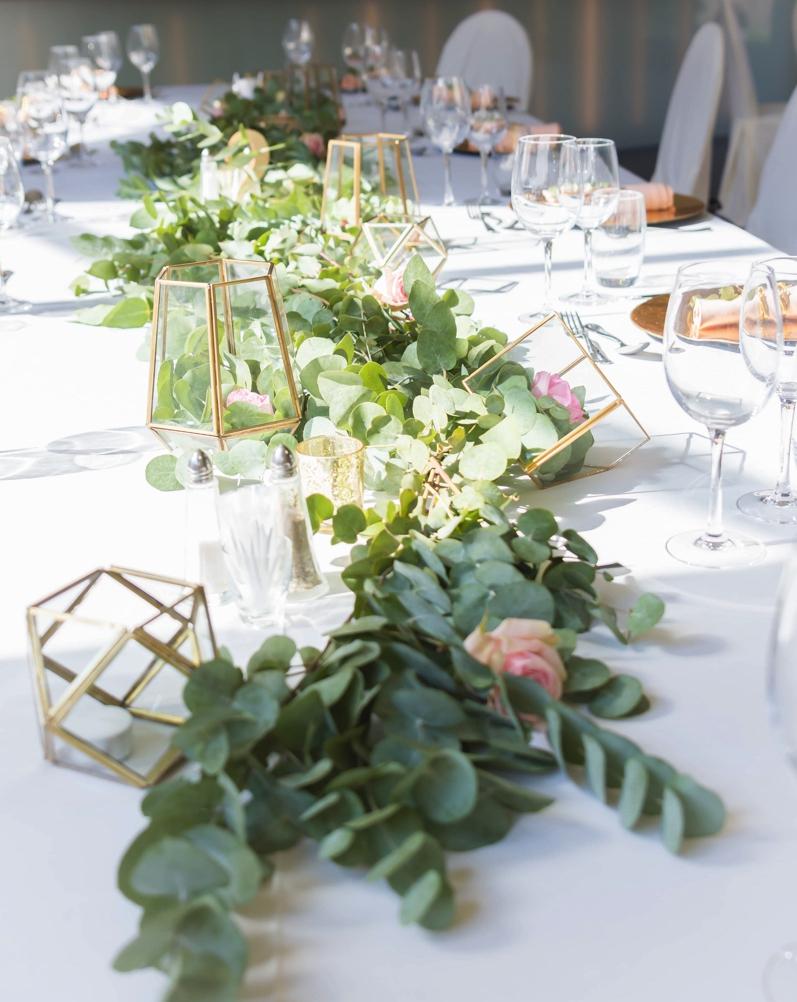 roze rozen en groene blaadjes in het midden van een gedekte tafel op trouwfeest