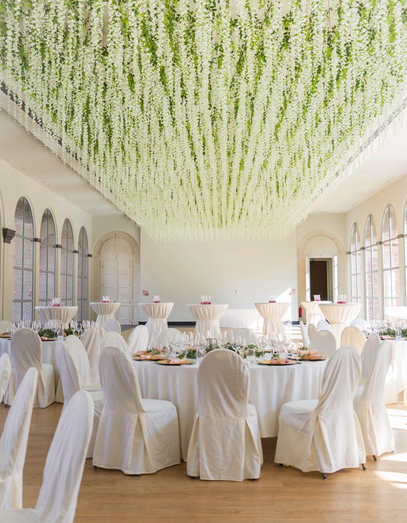 zaal met gedekte tafels en groene planten aan het plafond voor trouwfeest