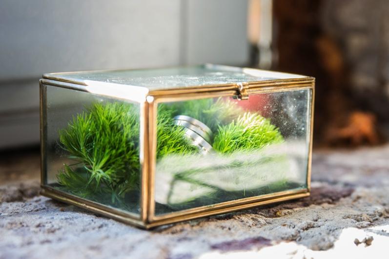 glazen doosje met mos en trouwringen