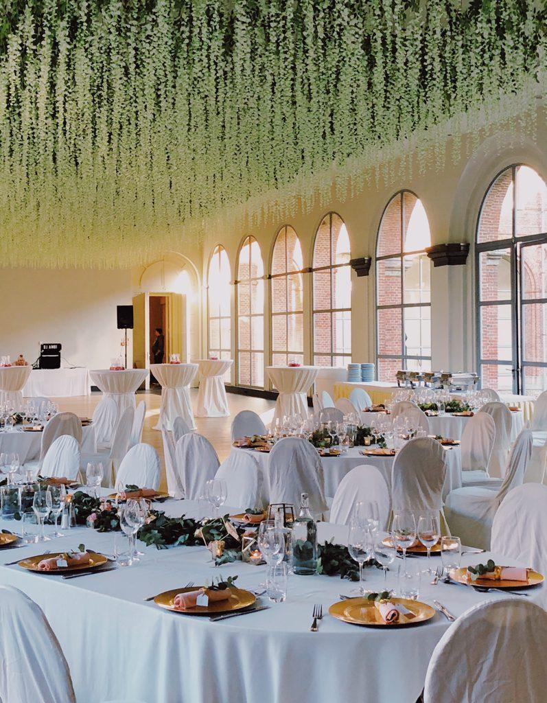zaal met gedekte tafels, groene plantjes aan plafond op trouwfeest