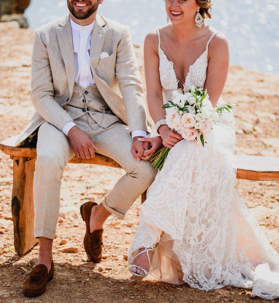bruid en bruidegom op bankje tijdens ceremonie op strand in Ibiza