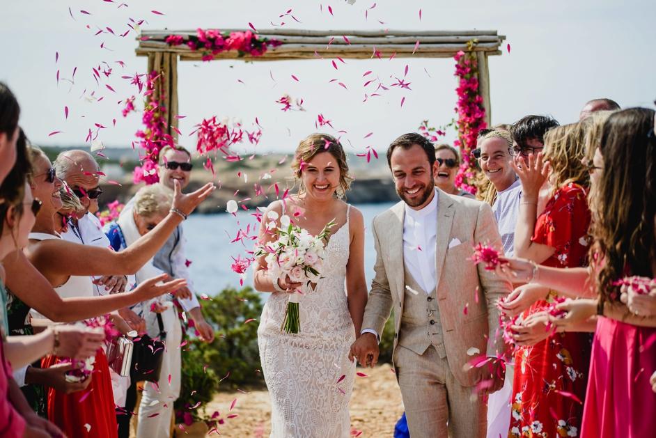 bruid en bruidegom die het gangpad afwandelen op strand in Ibiza met roze blaadjes die gegooid worden