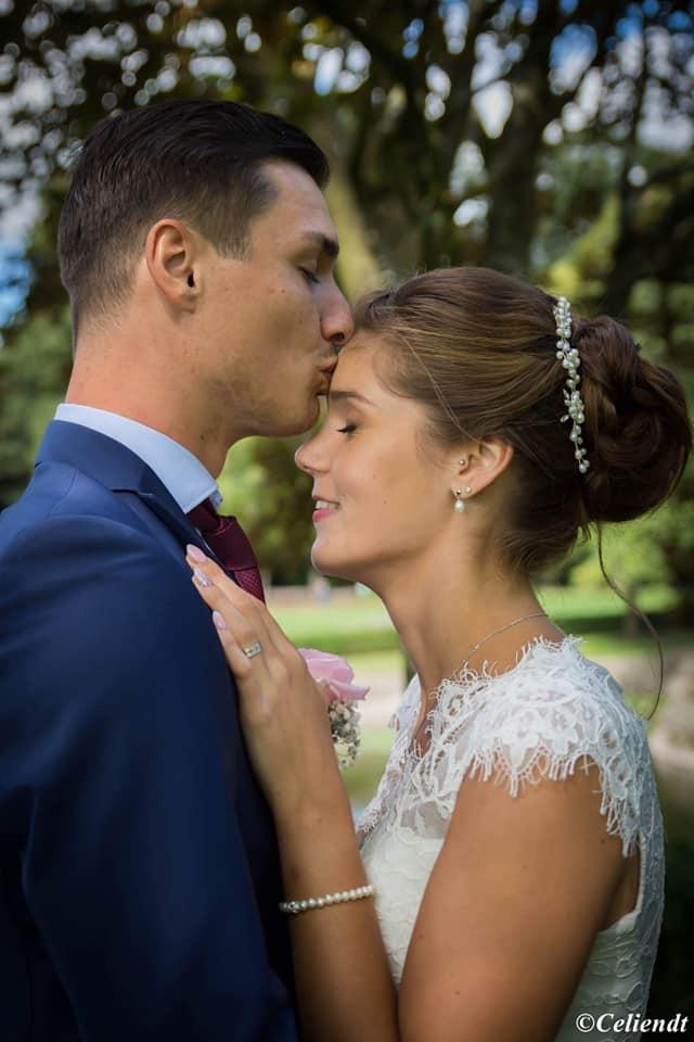 trouwfoto van bruidegom die bruid kust op voorhoofd