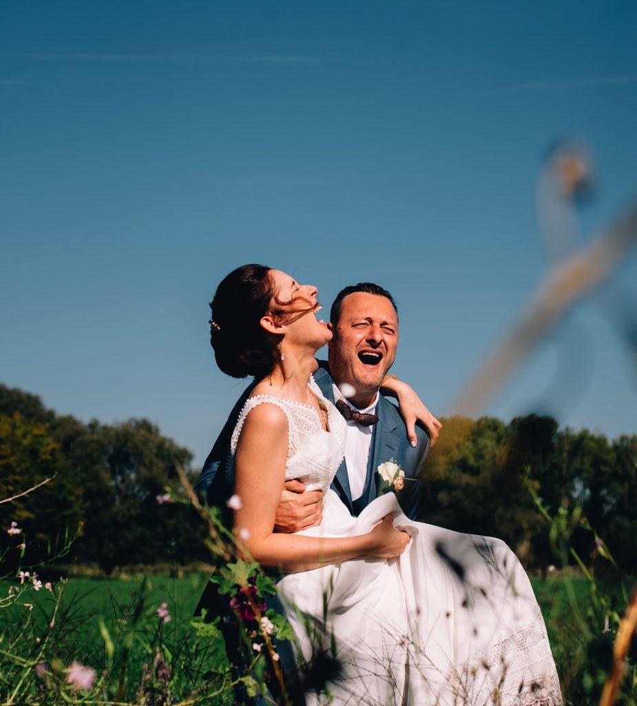 trouwfoto bruidegom die bruid draagt