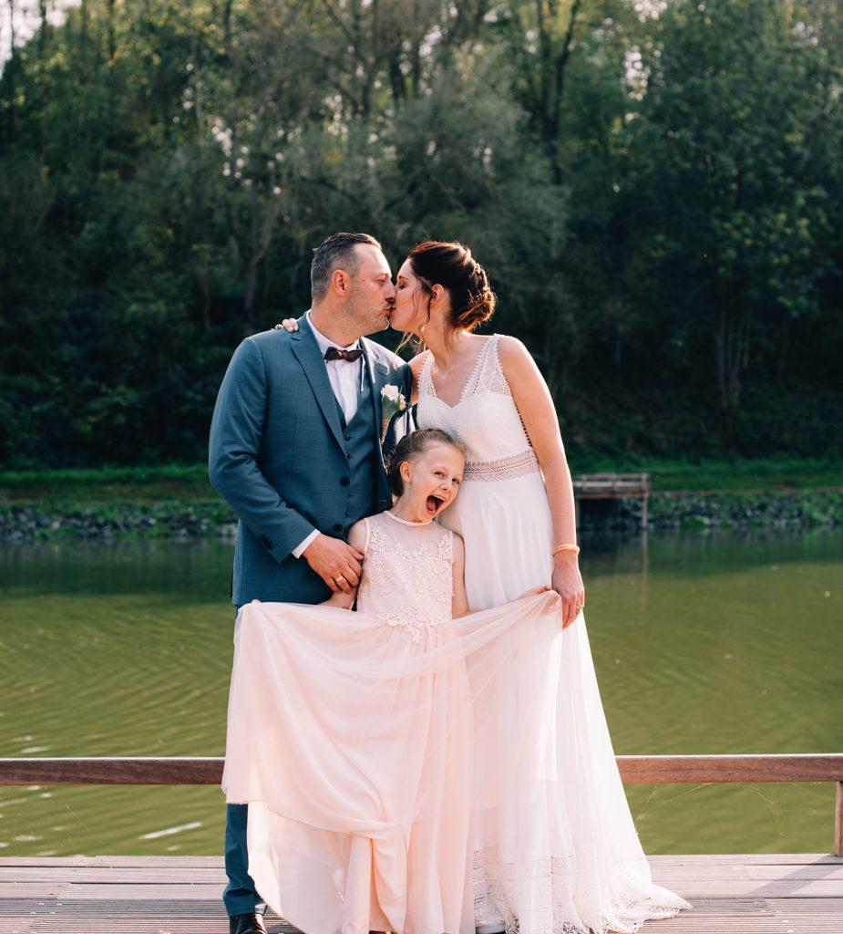 trouwfoto bruidspaar met bruidsmeisje op de voorgrond