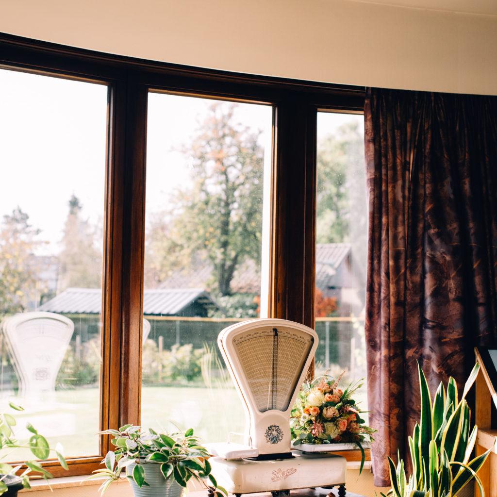 Oude weegschaal aan raam met planten rond