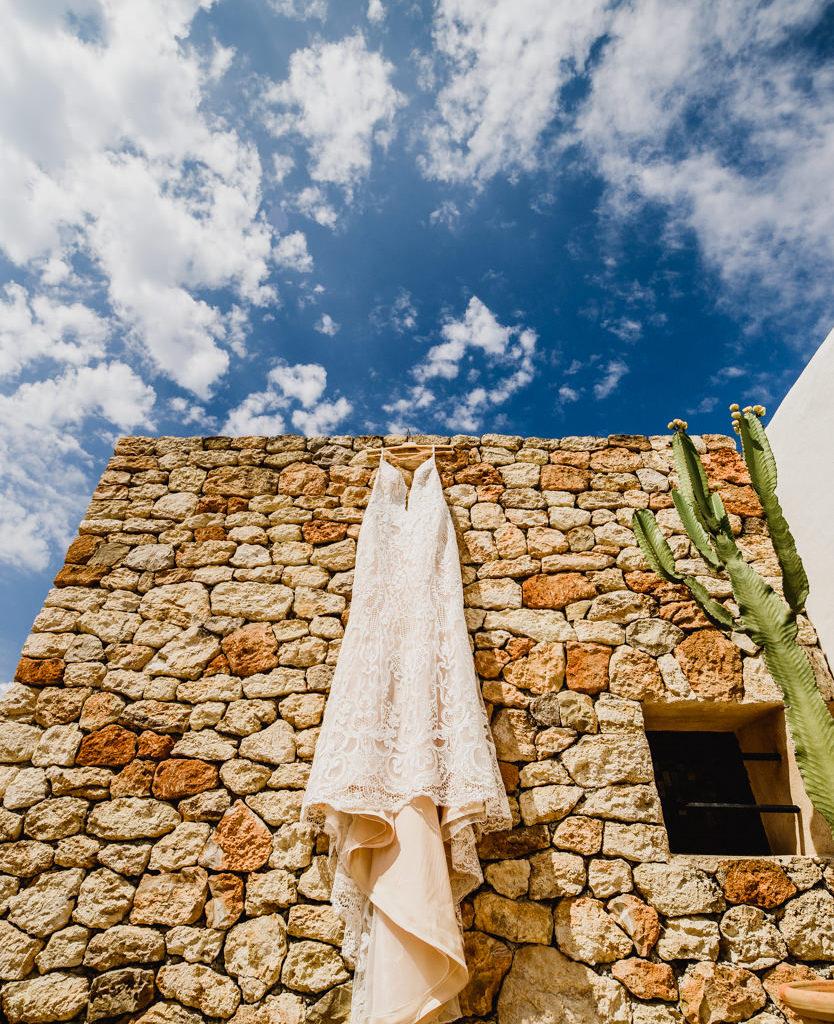 trouwkleed aan stenen muur met cactus