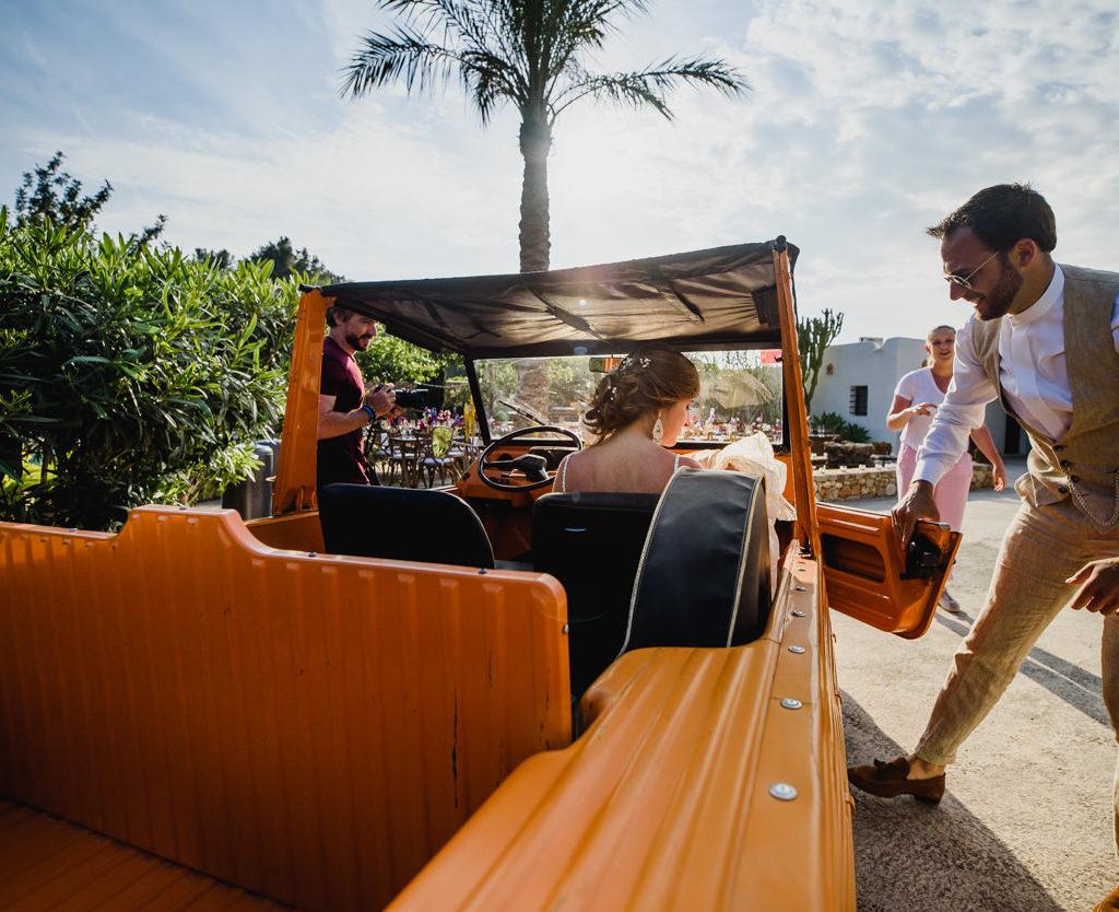bruidegom die deur opent van oranje jeep voor bruid