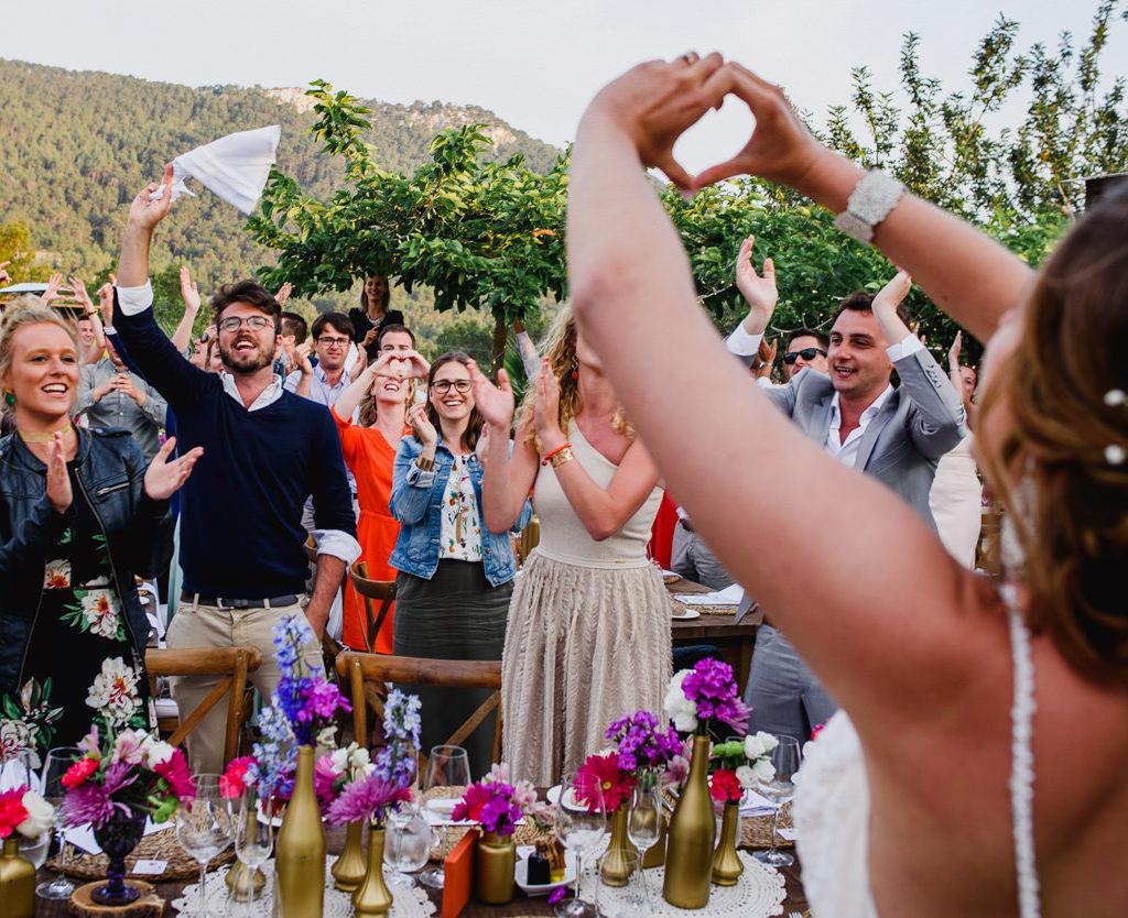 bruid die een hartje vormt met handen naar gasten