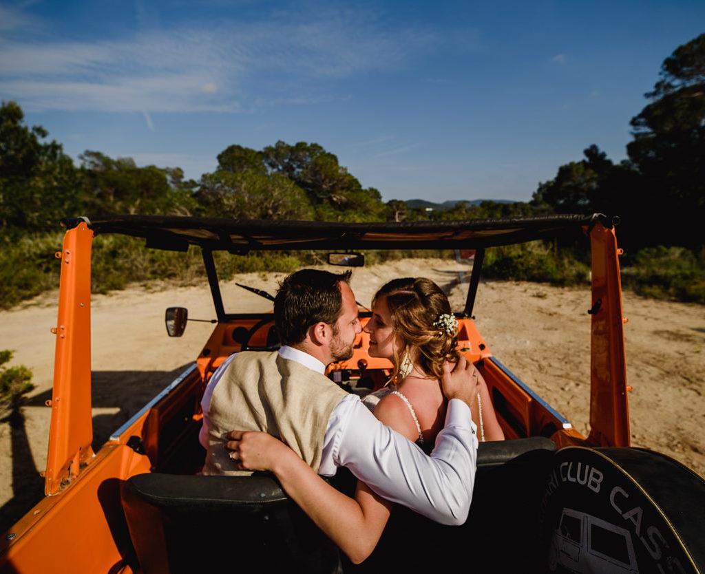 bruid en bruidegom die bijna kussen in oranje jeep