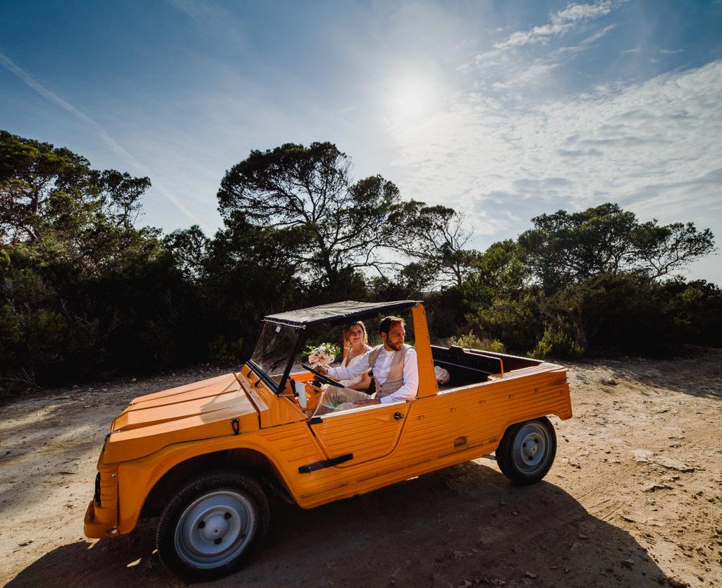 bruid en bruidegom in oranje jeep