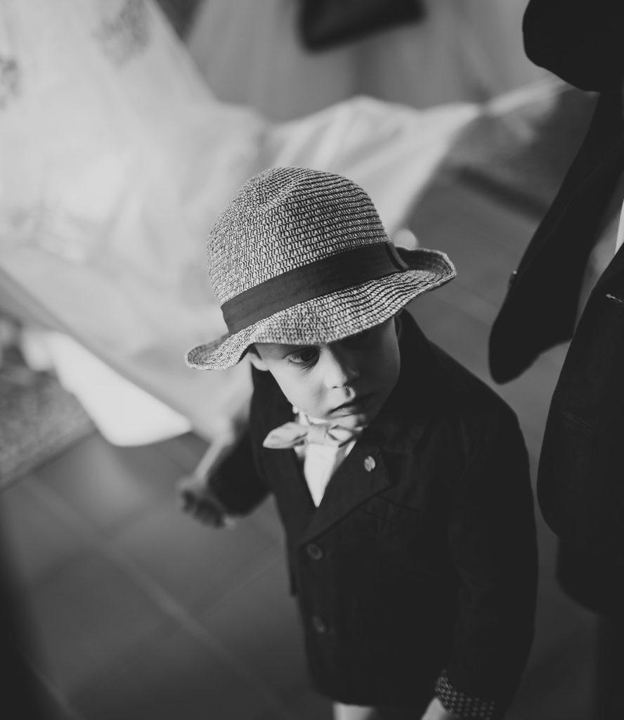 klein kindje in kostuum met hoed op trouw