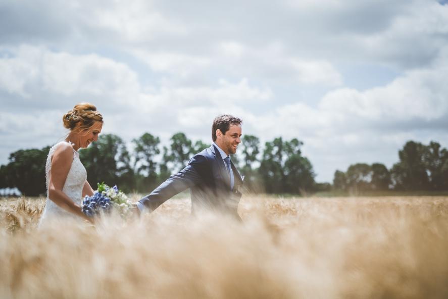 trouwfoto van bruid en bruidegom die door graanveld lopen