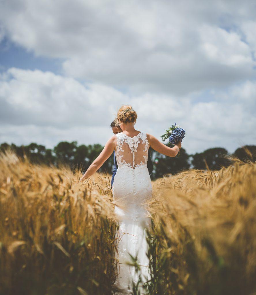 trouwfoto van bruid die door graanveld loopt