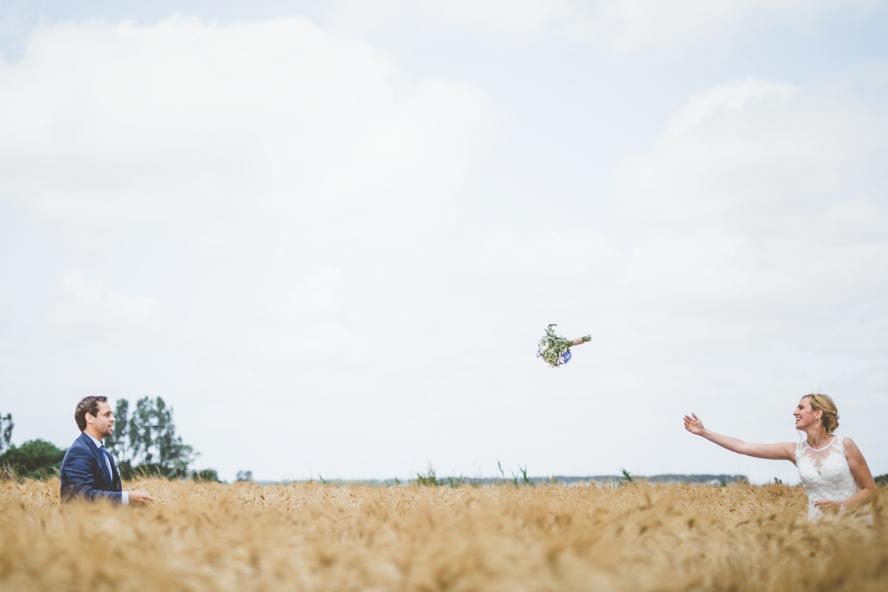 Foto van bruid die haar boeket in graanveld gooit