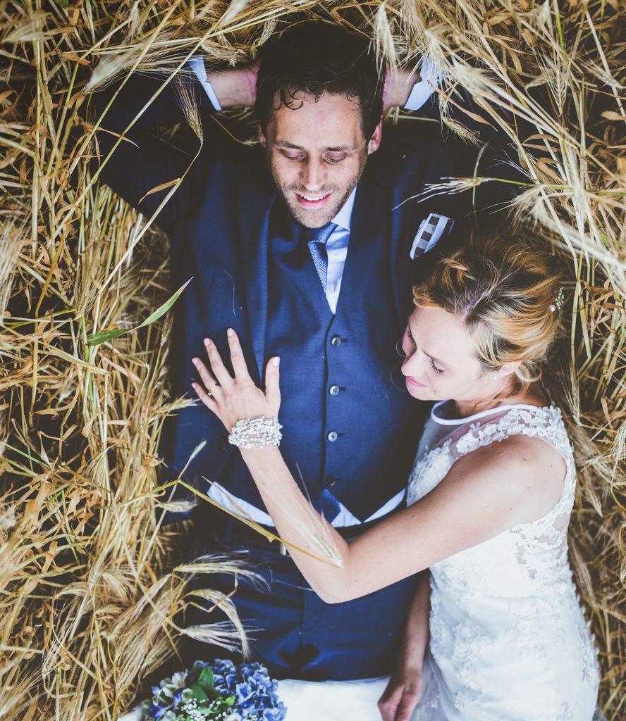 Trouwfoto van bruid en bruidegom liggend in graanveld
