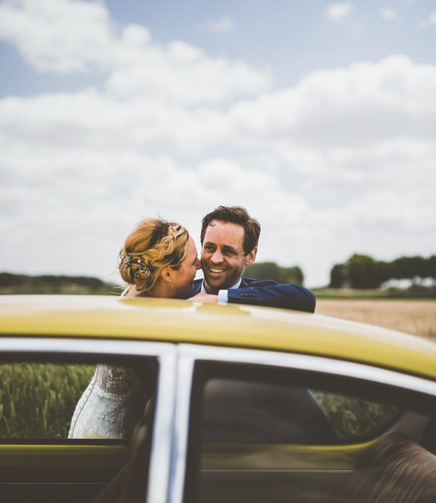 Trouwfoto van bruid en bruidegom achter een gele auto
