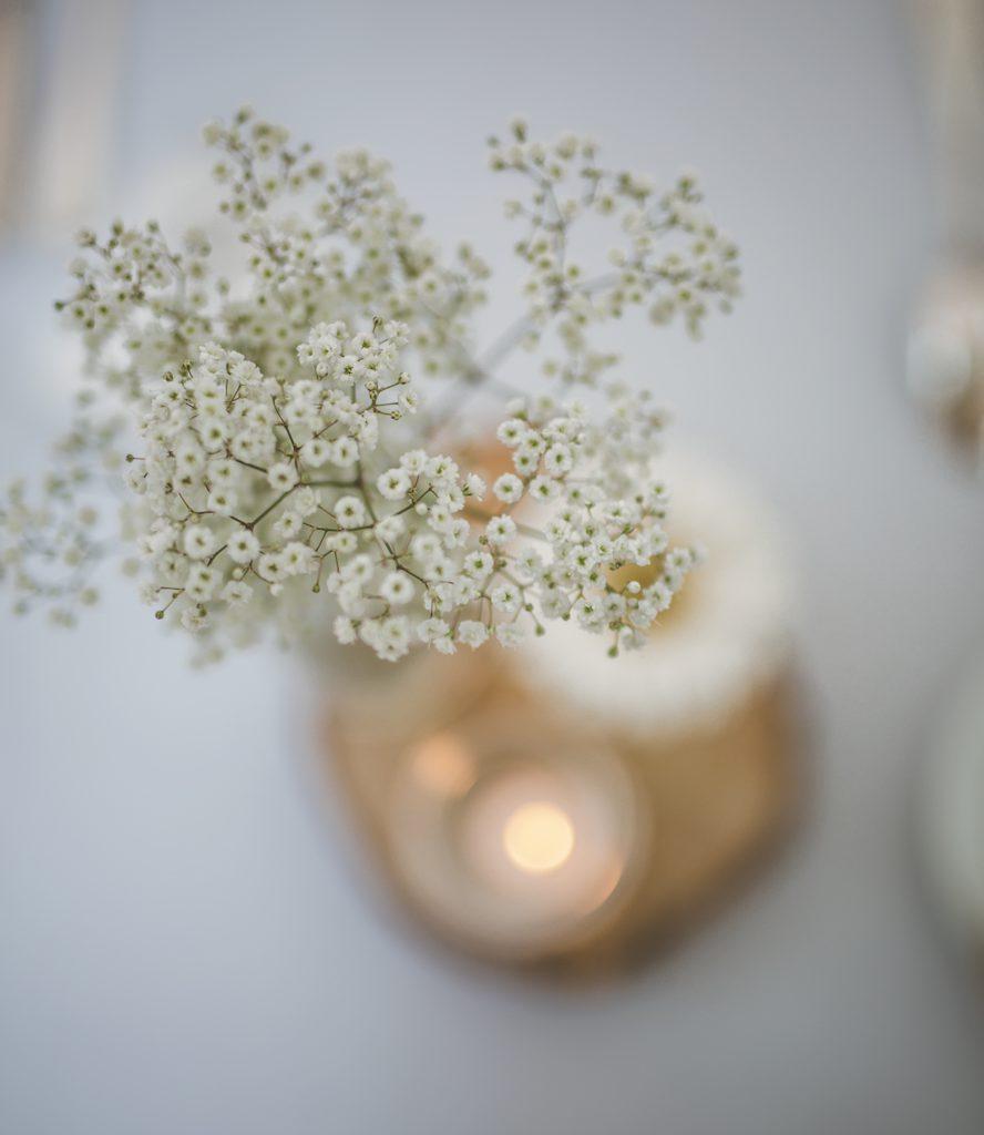 Bloemstukje wit op houten schijf op huwelijkstafel
