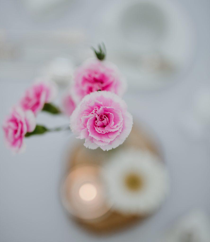 Bloemstukje roze op houten schijf op huwelijkstafel