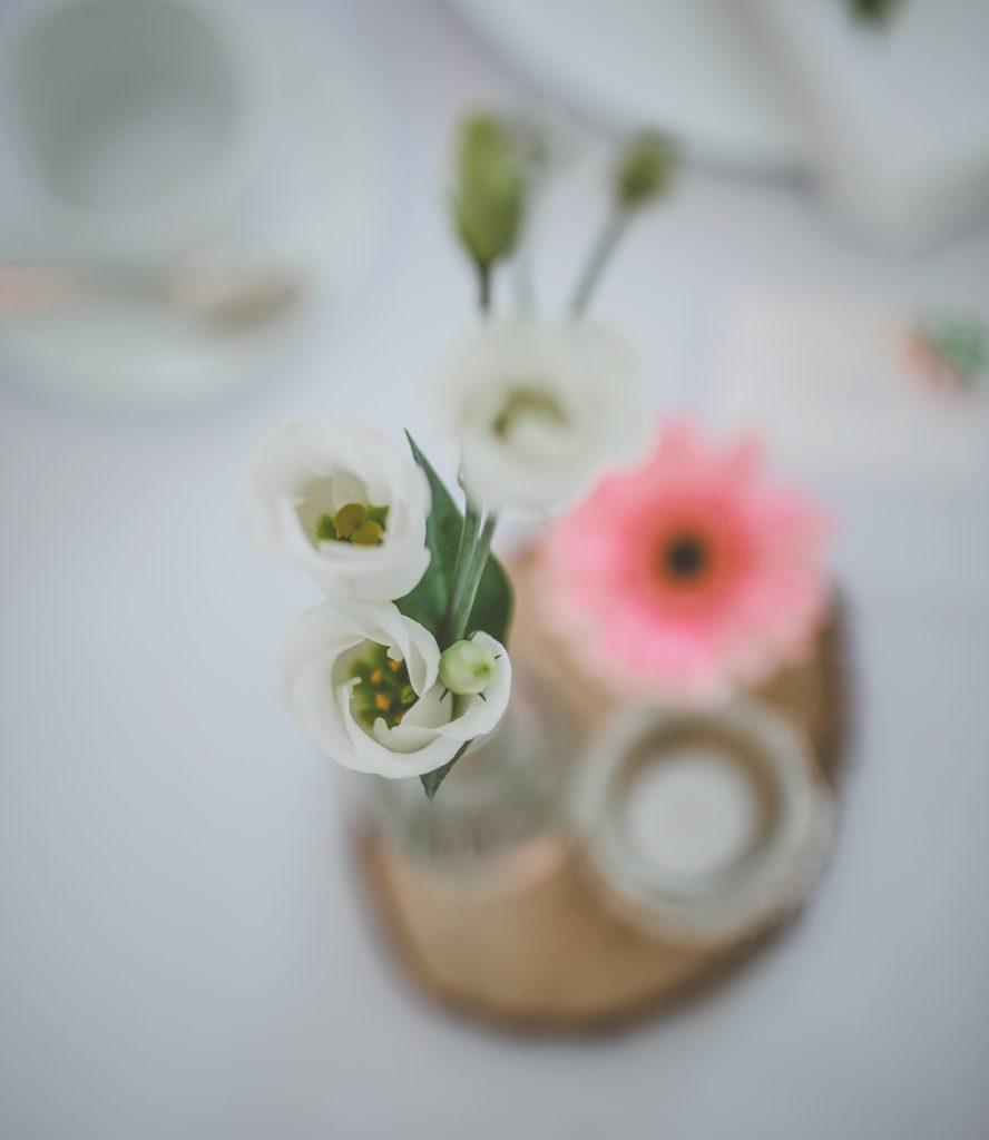 Bloemstukje roze en wit op houten schijf voor huwelijkstafel