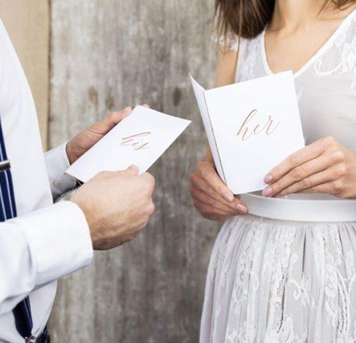 Bruid en bruidegom die gelofte boekjes vasthebben met 'His' en 'Her' op.