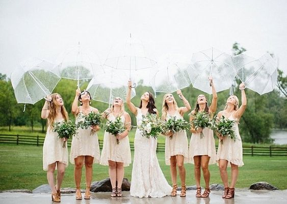 Bruid met 6 bruidsmeisjes in de regen met doorzichtige paraplu