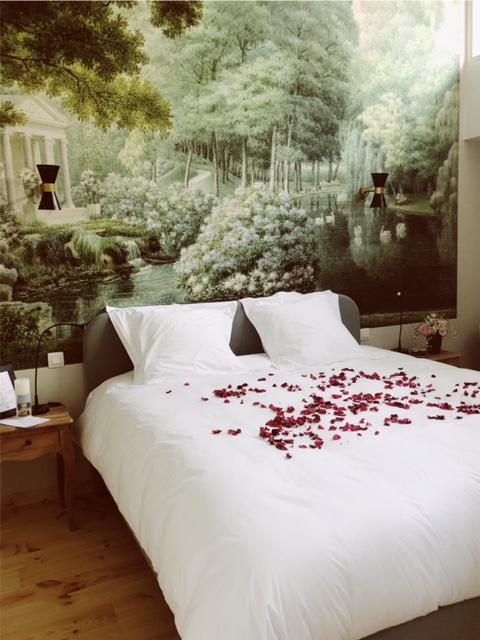 Wit bed met rode rozenblaadjes