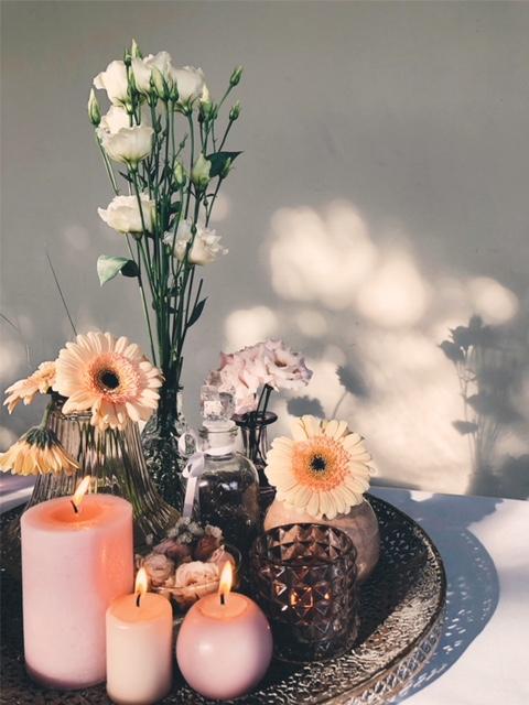 Vazen met bloemen en kaarsen met roze tinten