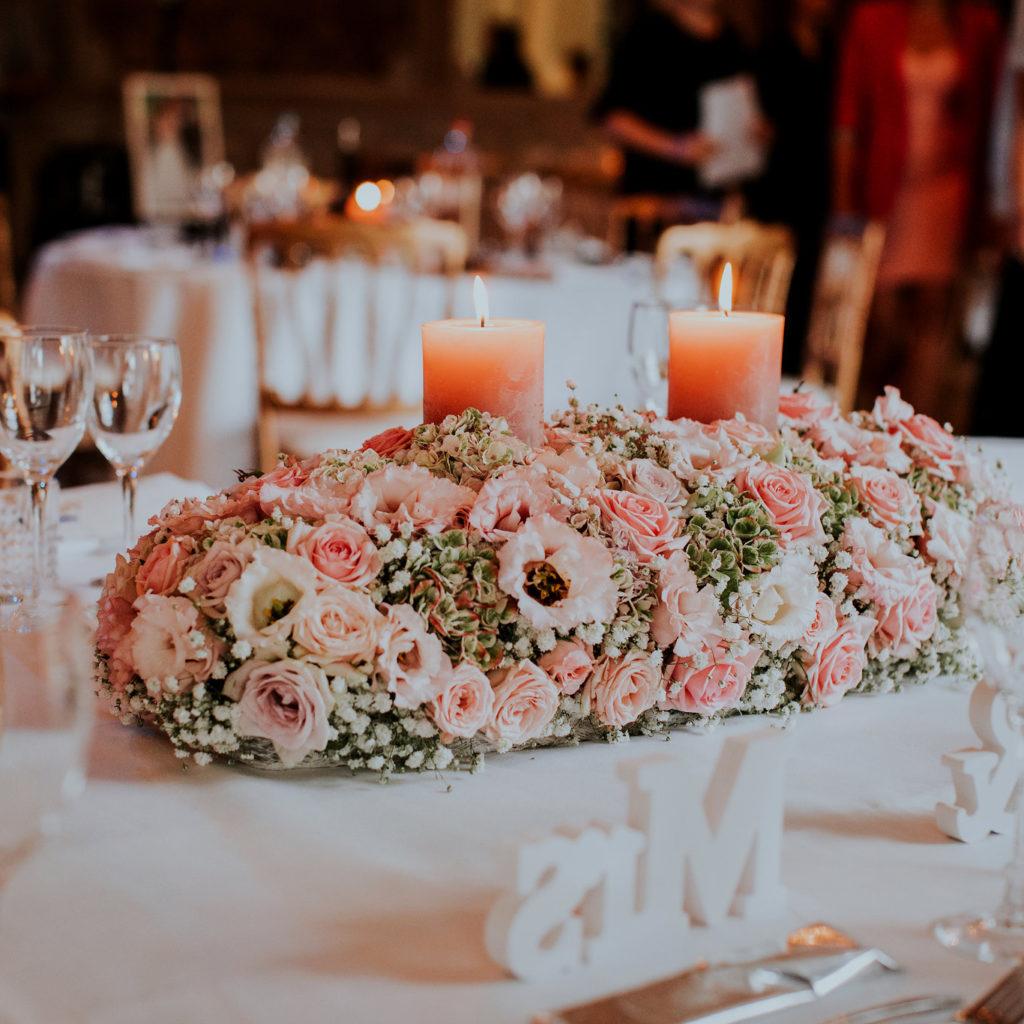 Bloemstukje met roze kaars op huwelijkstafel