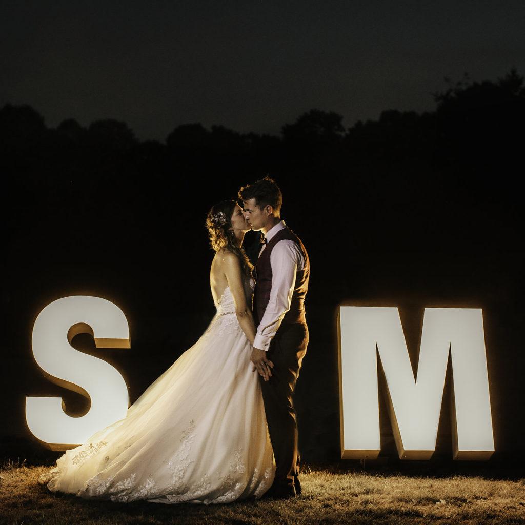Lichtgevende letters 'S & M' huwelijk met bruid en bruidegom tussenin