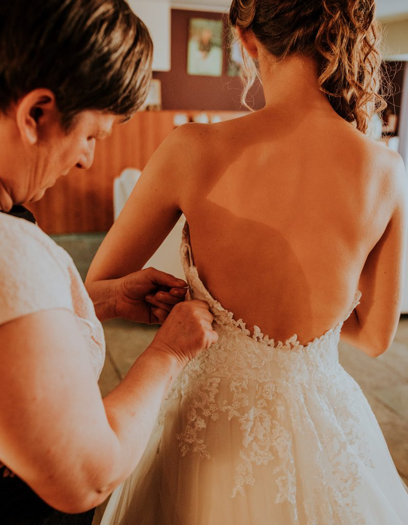vrouw die bruidsjurk vastmaakt