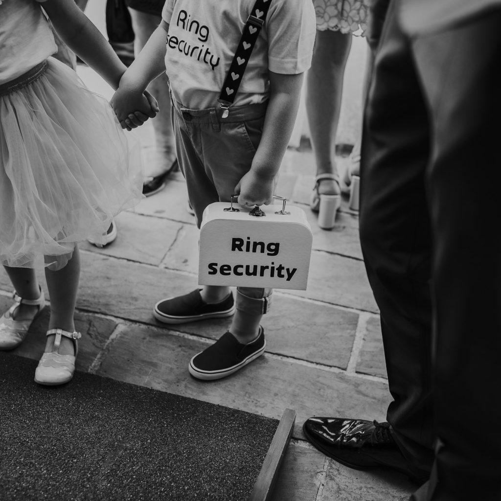 bruidskindjes die handjes vasthouden en oude brooddoos met 'ring security' op