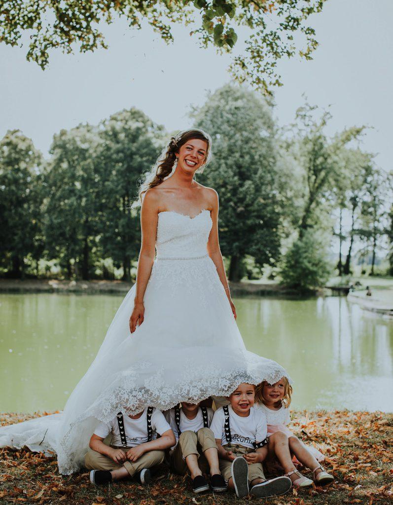 vier kindjes onder kleed bruid