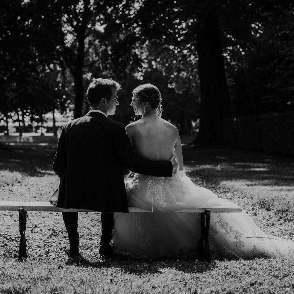 achterkant bruidspaar zittend op bankje