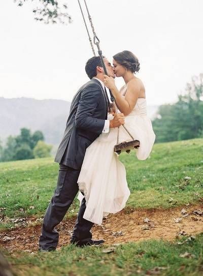 Bruid op schommel die gekust wordt door bruidegom