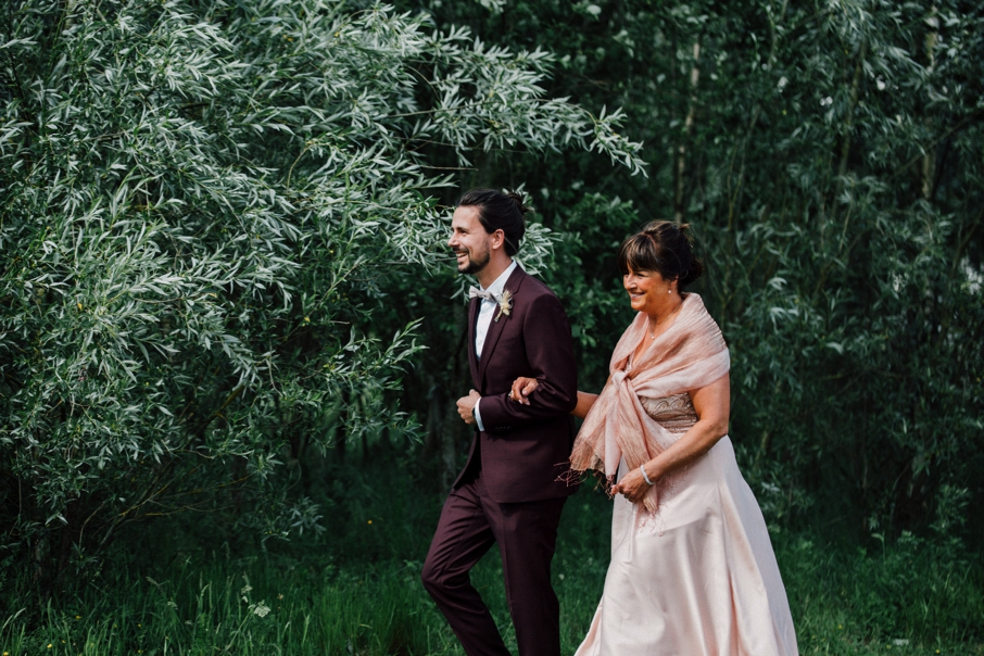 Bruidegom loopt met mama naar het altaar